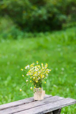 Hermoso ramo de flores silvestres en un banco de madera sobre fondo de naturaleza de verano en el campo.