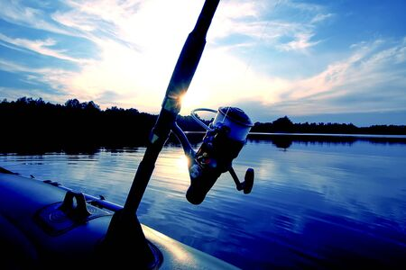 Spinning with reel on evening lake background.