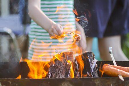 Child preparing marshmallow on wooden stick over a brazier