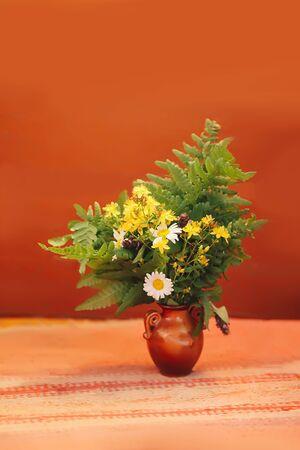 Hermoso ramo de flores silvestres de verano en jarrón de cerámica sobre estera hecha a mano. Foto de archivo