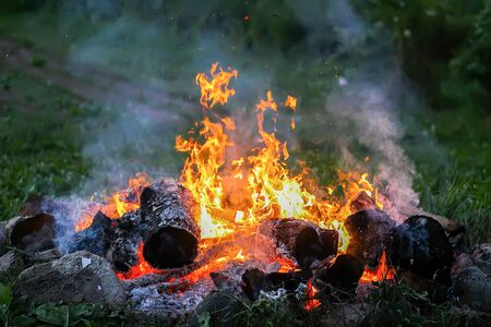 Bonfire at a camp in summer evening outdoors. Stock Photo