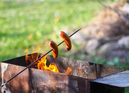 Hot sausages preparing on wooden stick over a brazier Archivio Fotografico