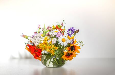 Beautiful bouquet of summer wildflowers in a transparent vase on white background.