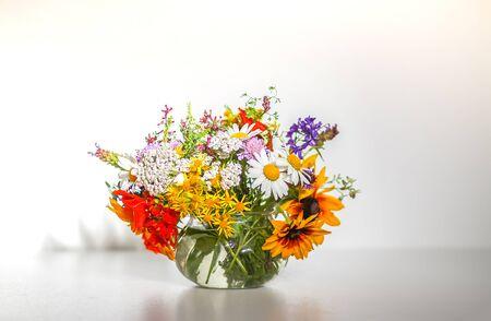 Hermoso ramo de flores silvestres de verano en un jarrón transparente sobre fondo blanco.