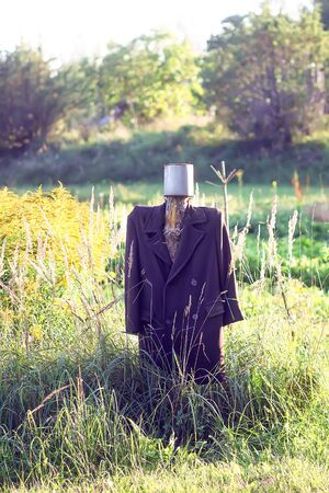 Funny handmade traditional scarecrow in rural field. 스톡 콘텐츠