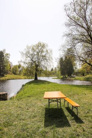 Beautiful spring landscape with green trees and wooden bench and table for rest near the pond in park