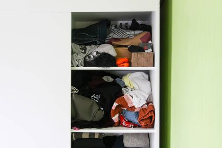 Disorder in wardrobe with colorful clothes. Different clothes thrown on a white shelf