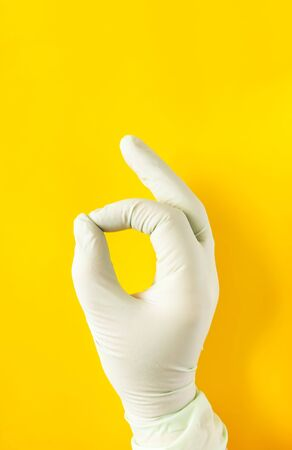Hand in rubber glove. OK sign on bright yellow background