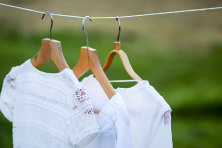 Linen dresses hanging on a wooden hangers outdoors in summer day