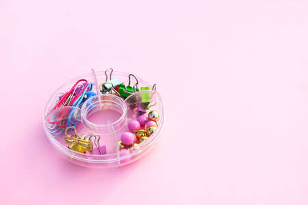 Colorful pins and paper clips in plastic round storage on pink soft background