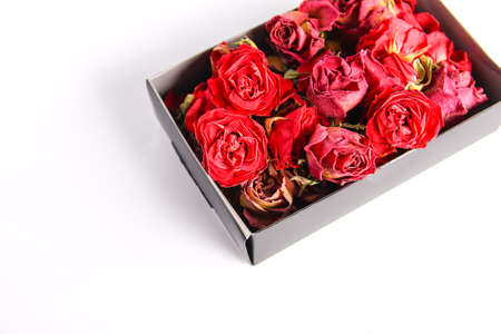 Red rose dried buds, flowers and petals in the opened cardboard box