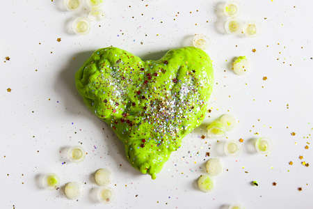 Green heart with shiny glitters made from slime by child 写真素材