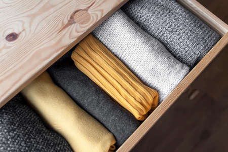 Open wooden dresser drawer with warm knitted woolen clothes. Home vertical storage. Wardrobe organisation. Trendy colors. Stock Photo