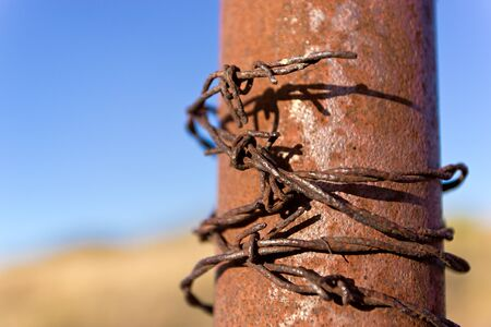 barbwire: Barbed wire wrapped around iron post Stock Photo