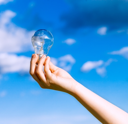 Hand Holding Brillant Bulb With Blue Sky Background  Stock Photo - 19323937