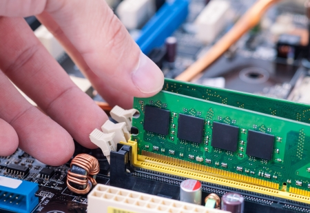 Hand Installing SDRAM Memory Module on PC Motherboard