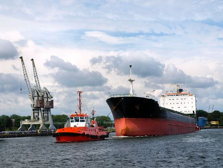 shipyard: Red tug is towing the vessel in port. Stock Photo