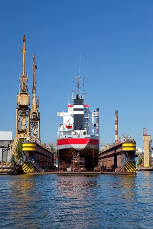 A large cargo ship is being renovated in shipyard Gdansk, Poland.