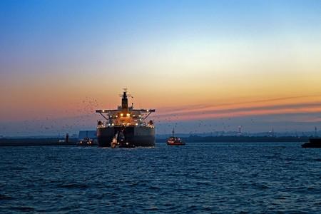 Travailler en mer après le coucher du soleil - un cargo pénètre dans le port, escorté par des remorqueurs. Banque d'images