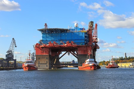 The introduction of a drilling rig to a shipyard for repairs.  photo