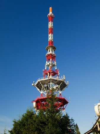 Communication antenna tower and satellite dish against blue sky photo