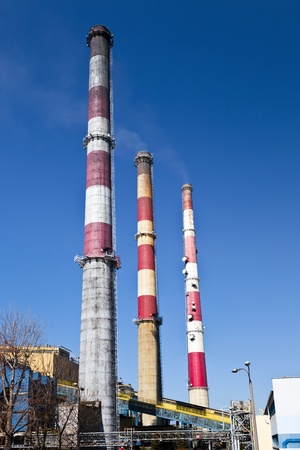 Big power plant with three high chimneys.