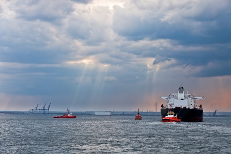 tug: Maneuvers at sea on a cloudy day - Escorting tanker by tugs.