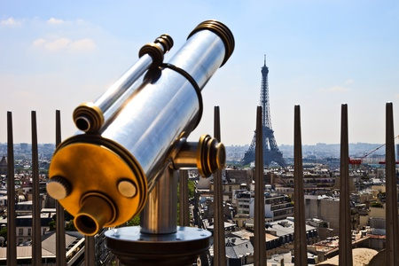 A bright and shiny telescope on the Arc de Triomphe in Paris with the Eiffel Tower in the background. photo