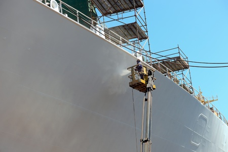 commercial docks: Worker painting ship hull using airbrush.