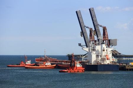 Tug boats pushing a cargo ship to port. photo