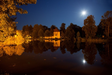Church on the water at night in Zwierzyniec, Poland. photo