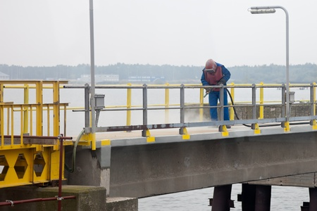 Worker sandblasting barrier on the waterfront. Stock Photo - 10753142