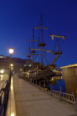 Old sailing ship at the wharf at night.