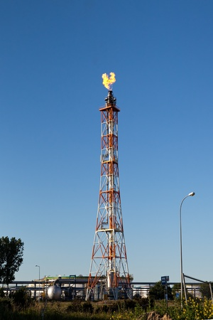 tall chimney: Flare burning gas at refinery with tall chimney against blue sky.