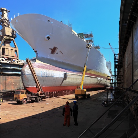 hull: A large cargo ship is being renovated in shipyard Gdansk, Poland.