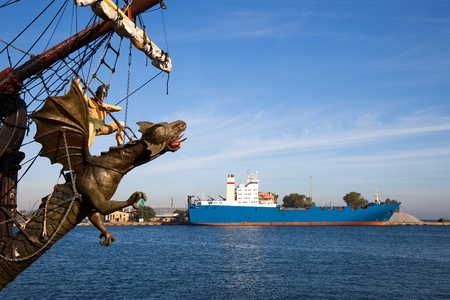 Ship in port on the background of the sculpture of the dragon knight. Gdynia, Poland.