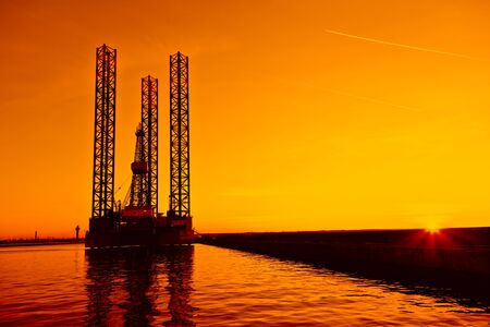 mineral oil: Oil rig at sunset background. Editorial