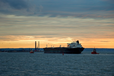 Large oil tanker with two tugs