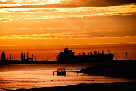 Tanker ship on the background of the rising sun.  photo