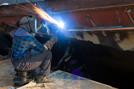 Welder in a protective mask when working. Photo taken on: August 26th, 2011