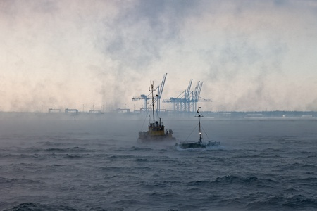 Barge at sea on a cold foggy day struggling with the waves. photo