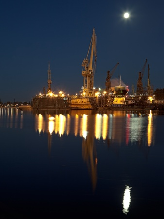 cargo vessel: Dry dock in the moonlight at the shipyard in Gdansk, Poland  Stock Photo