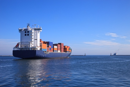 Container ship departs from a port in the sea