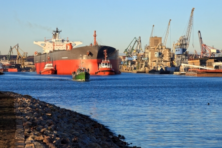 escorted: A large tanker leaves a port, escorted by tugs. Gdansk, Poland.