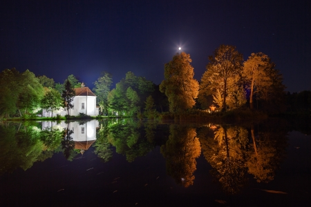 crescent lake: Church on the water at night in Zwierzyniec, Poland.