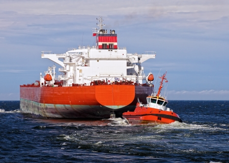 tug boat: Tugboat towing a large tanker