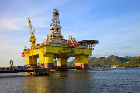 torre de perforacion petrolera: Plataforma petrolera cerca de las montañas de Noruega.
