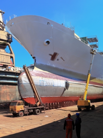 dockyard: A large cargo ship is being renovated in shipyard. Editorial