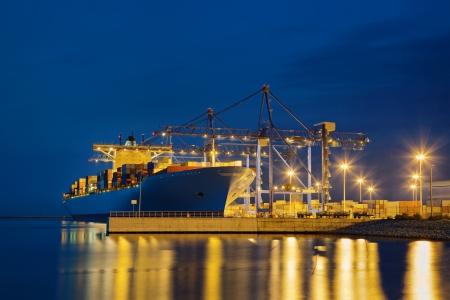 Groot vrachtschip bij het laden in de haven 's nachts