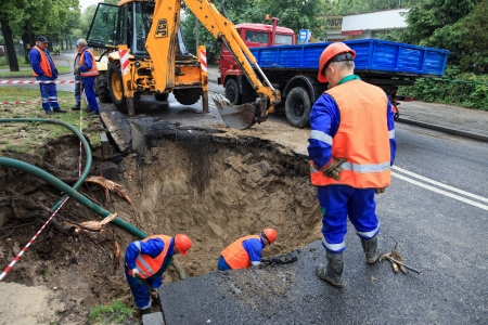destruct: GDANSK, POLAND - JUNE 22: Workers repairing the damaged road after rupture pipe that caused the congested city during the Euro 2012 Championship Editorial